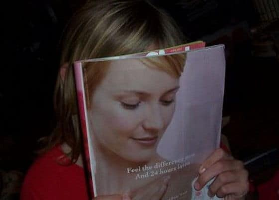 Womans face behind a magazine blends into magazine