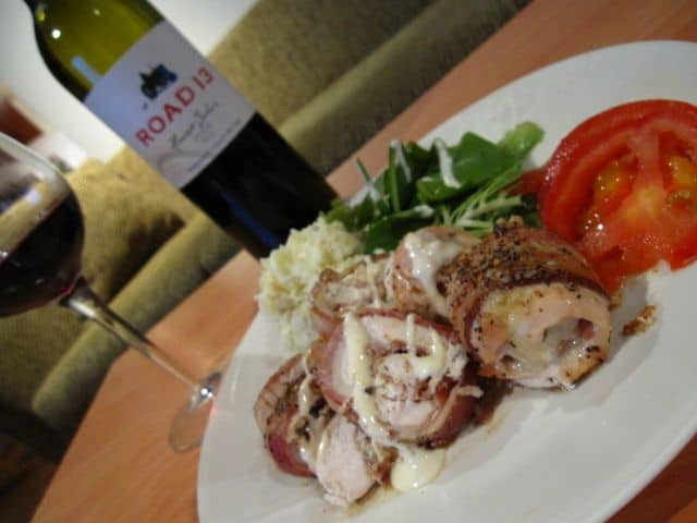 The Finished Chicken Wrapped Bacon On A Plate With Red Wine