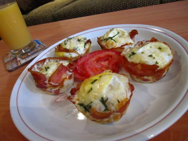 Eggs wrapped in bacon finished on a white plate with orange juice