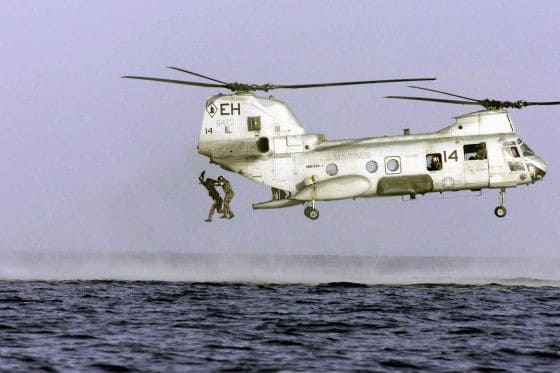 Marines jumping out of a CH-46 Sea Knight helicopter into the water