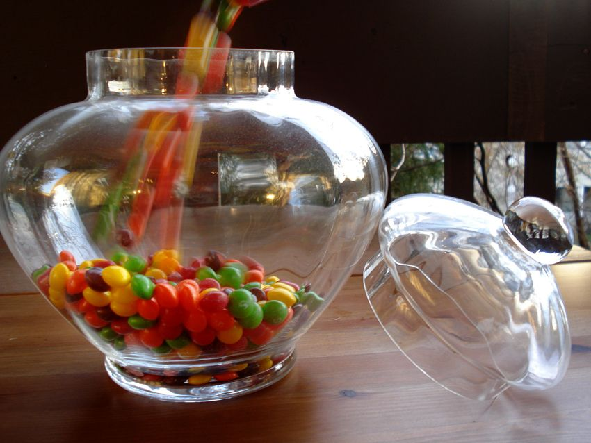 Skittles pouring into a glass jar for skittle vodka