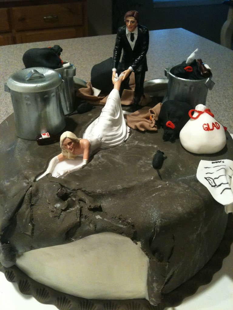 man pulling woman by foot on divorce cake