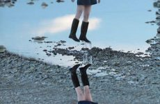 pretty japanese girl floats above her reflection in a puddle