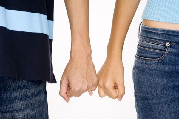 man and woman with pinky fingers linked