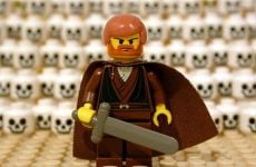 lego man standing in front of a wall of skulls