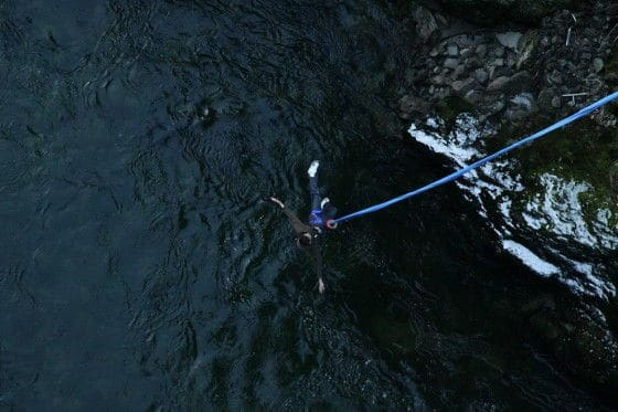 Bungee jumper dips into the river below