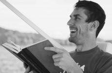 man laughing reading book