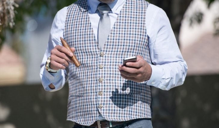 businessman using mobile phone and holding cigar