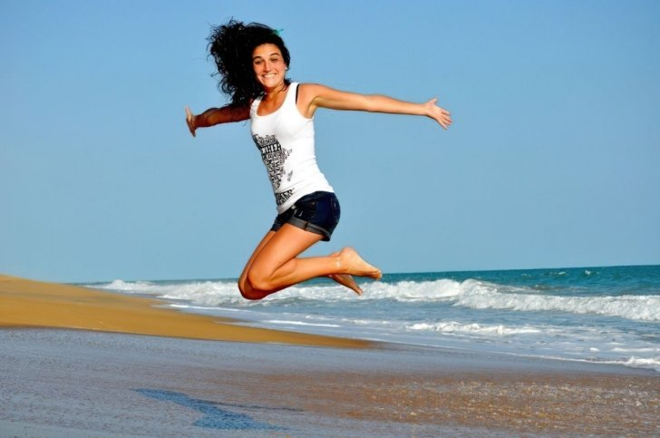 happy young woman jumping on beach enlarged