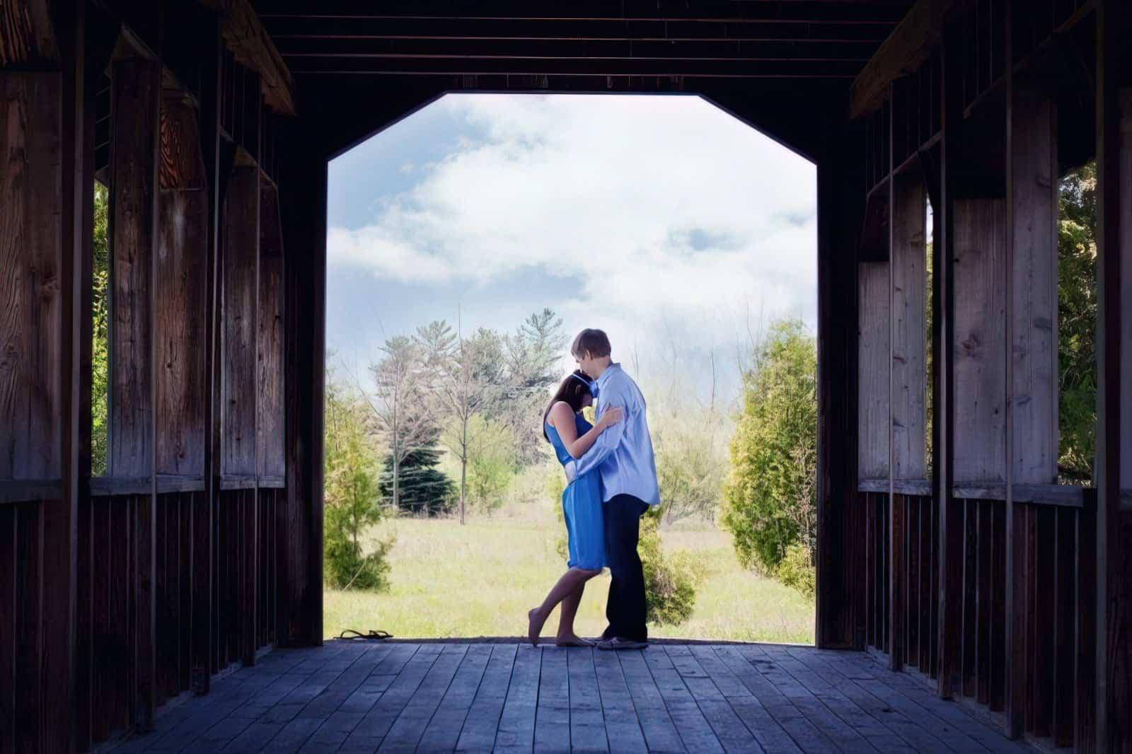 hugging couple covered bridge girlfriend boyfriend daylight