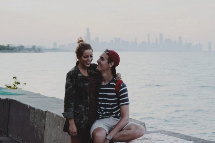 young couple sitting on ledge embracing and smiling happy