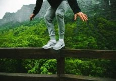 young man standing on fence with bush and mountains in background