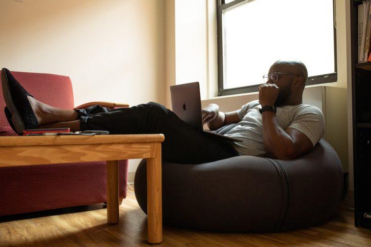 man sitting in beanbag chair