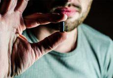 man holding black pill