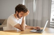 stressed person looking at computer upscaled