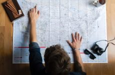 person pointing at paper map