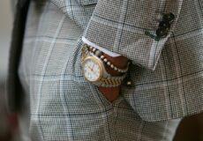 man wearing fancy watch and pearls