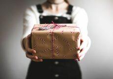 woman handing man a gift