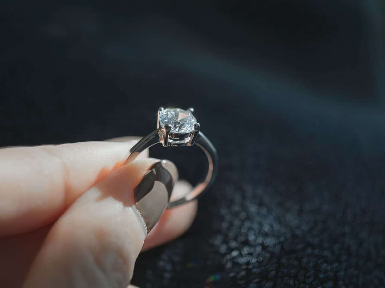 woman with black nails holding diamond ring